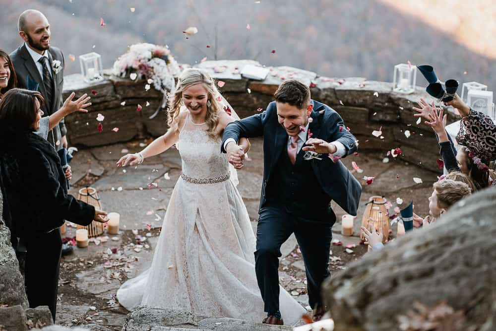 Couple walking under thrown flower petals