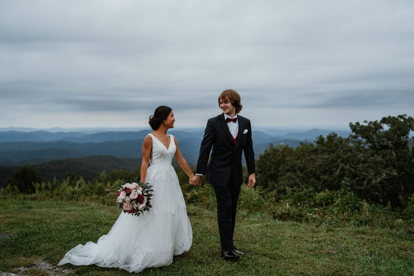 newlyweds holding hands in front of the blue ridge mountains