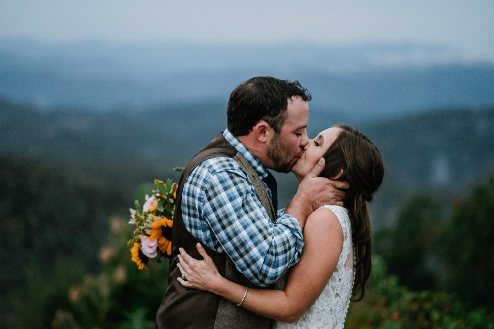 bride and groom kissing in front of the blue ridge mountains