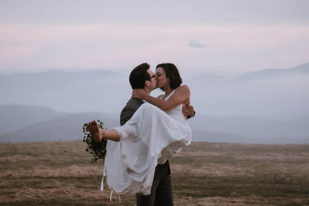 Groom holding his bride while they kiss with the Appalachian mountains in the background