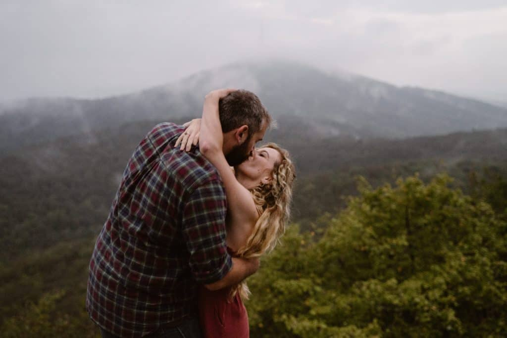 a couple embracing in front of the blue ridge mountains