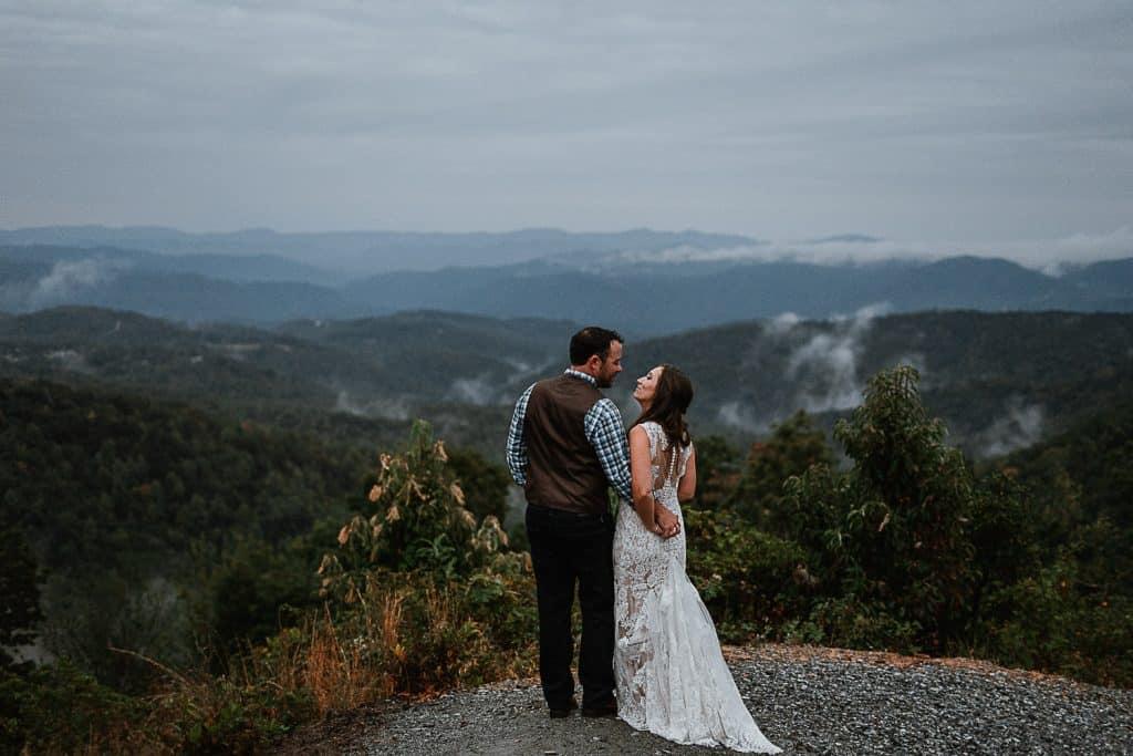 Newlyweds gazing at each other while they stand in front of mountains dappled with clouds