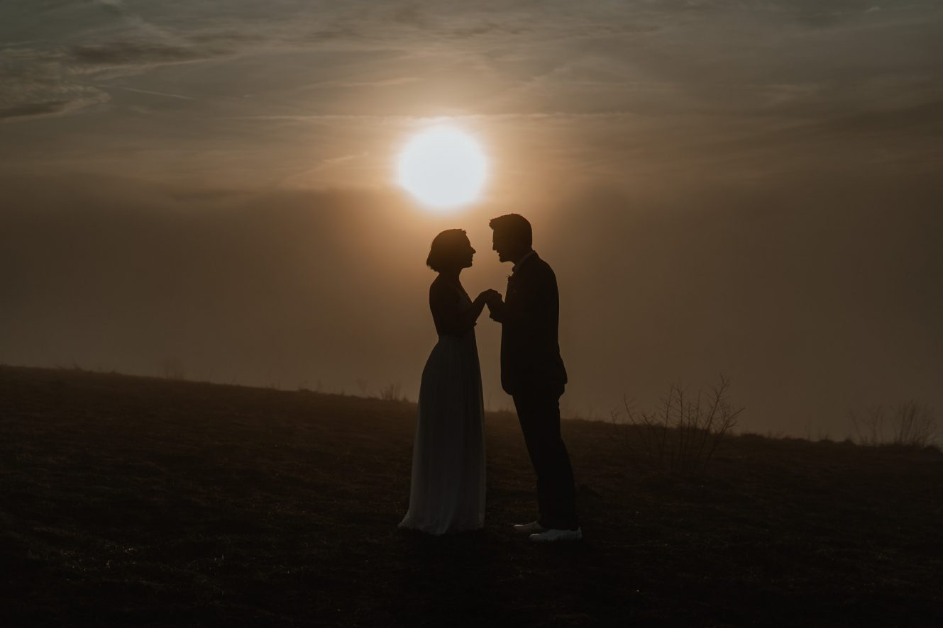 Couple holding hands during sunset in front of the Blue Ridge Mountains