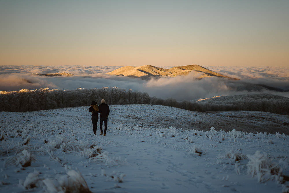 A couple walks down the snowy max patch hill
